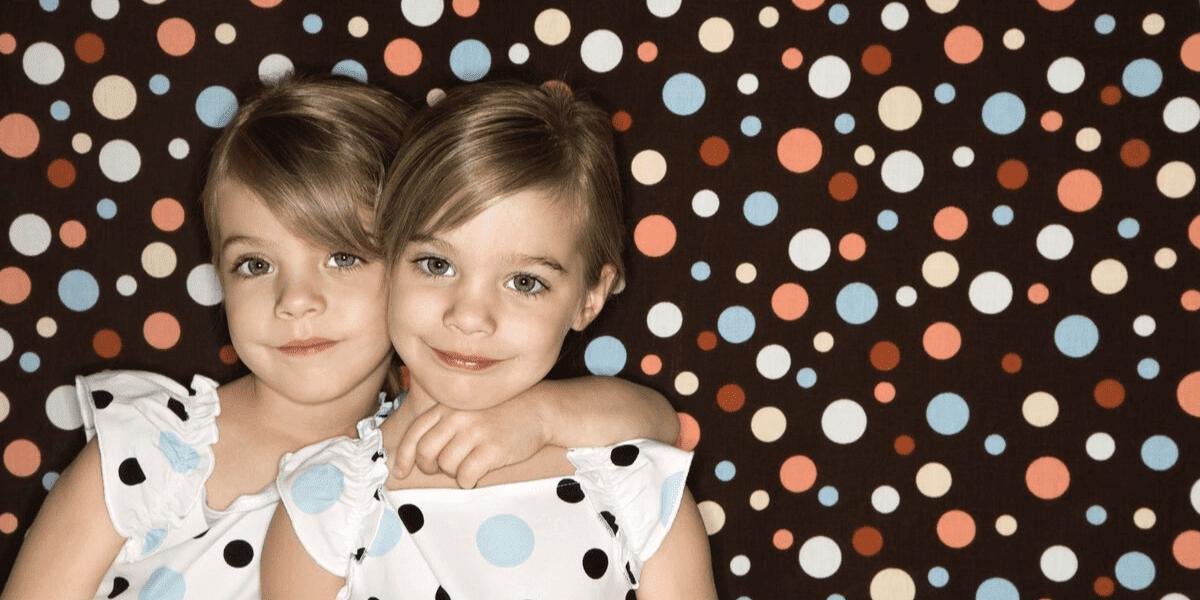 bliźniaczki ubrane tak samo na tle w kropki spersonalizowana bajka dla bliźniąt