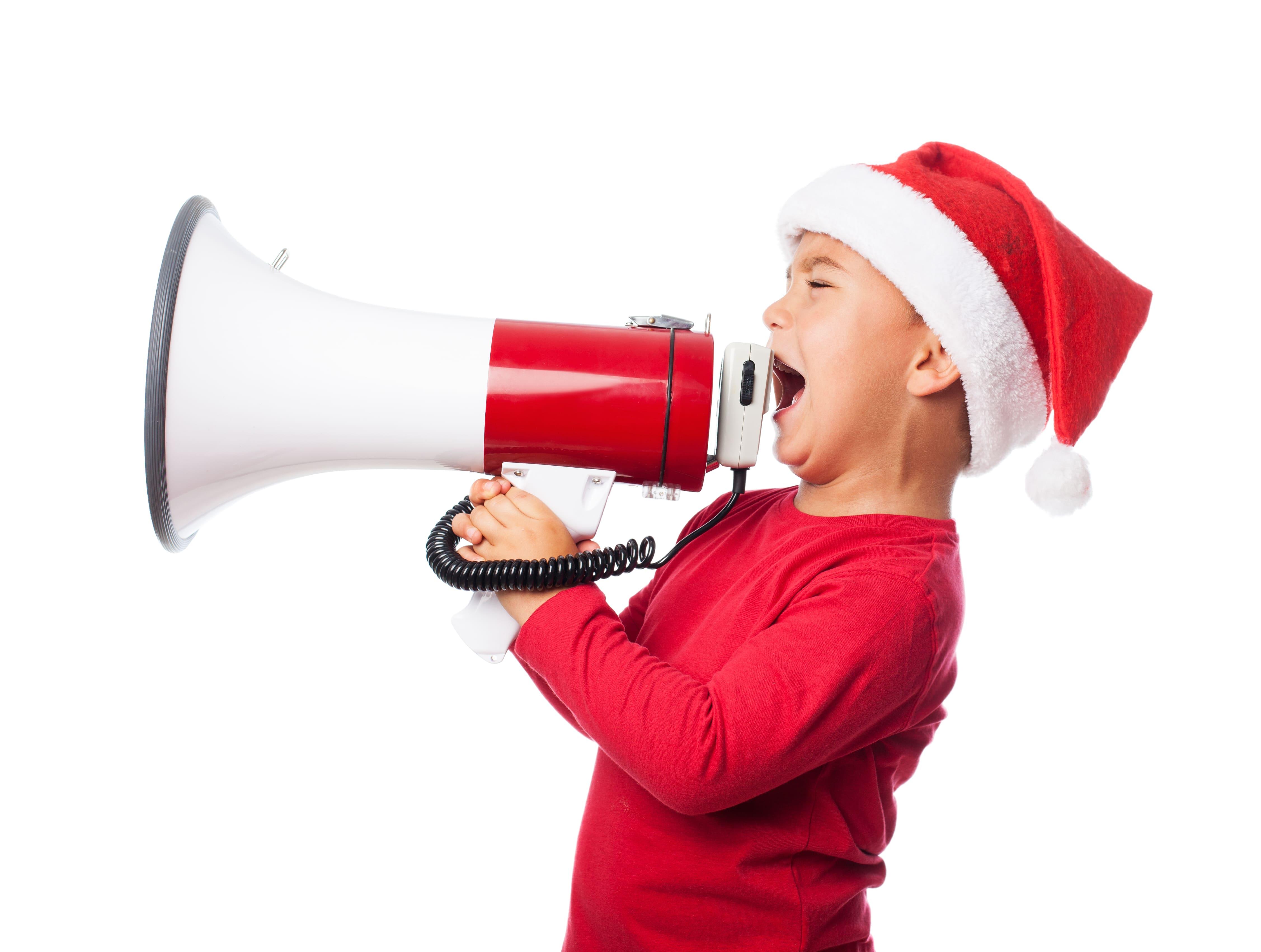 chłopiec w czapce Mikołaja z megafonem